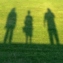 Shadow of three people standing outside