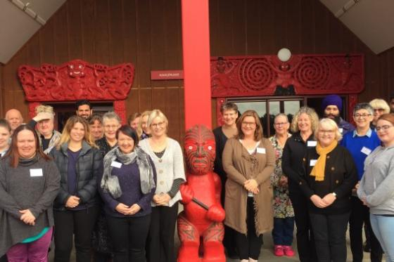 A group of Support Workers standing in front of a marae