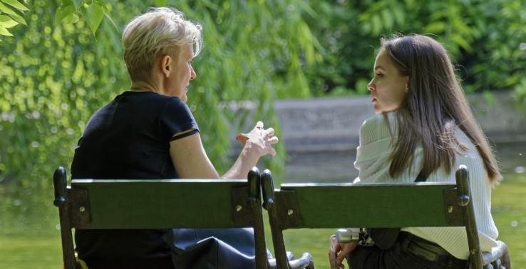Two women sitting outside talking together