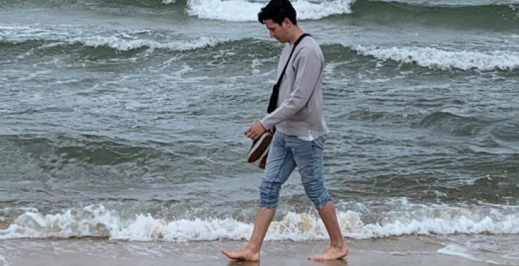 Man walking along beach in bare feet, jeans rolled up with waves in the background
